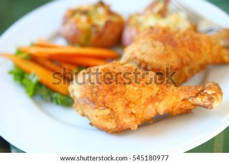 Closeup of fried chicken legs with roasted carrots and crushed potatoes