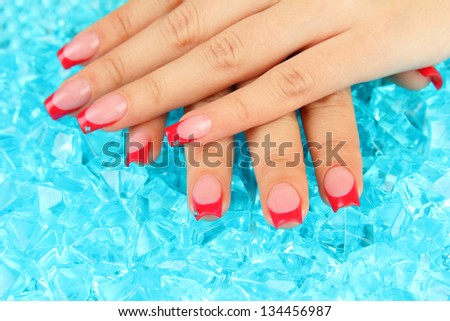 Closeup of hands of young woman with elegance manicure on bright background