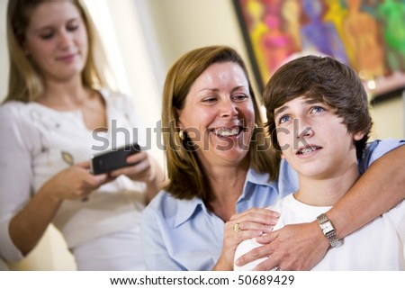 Closeup of loving mother with arm around teenage son smiling