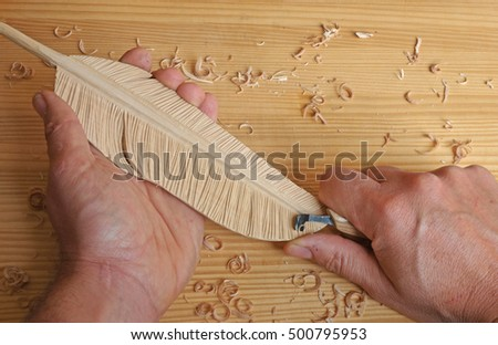closeup of male hands holding tool to carve a feather in wood