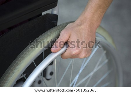 closeup of man in wheelchair holding the wheel