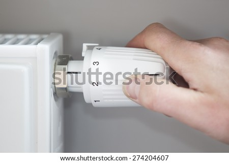Closeup of man's hand adjusting thermostat at home