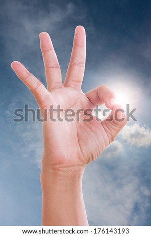 Closeup of man's hand gesturing - showing sign ok (okay) Ok in sky.