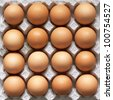 Closeup of many fresh brown eggs in carton tray - stock photo