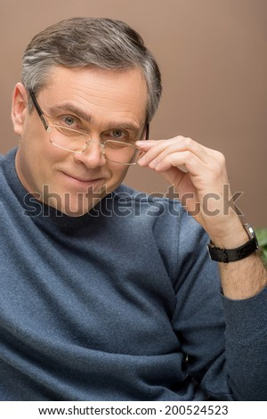 closeup of older man looking into camera. man wearing glasses and watches and smiling