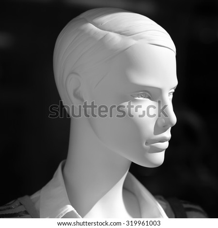 Closeup of one white realistic plastic imitating human body mannequin female face in shopping showcase standing in light on dark background, square picture
