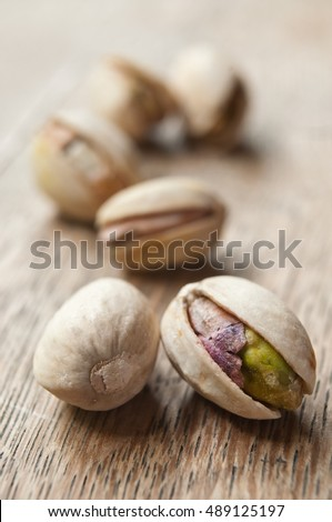 closeup of pistachios on wooden background