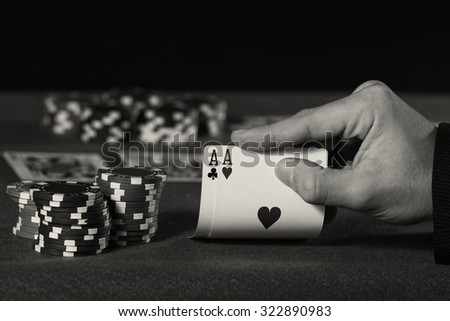 Closeup of poker player with two aces in black and white
