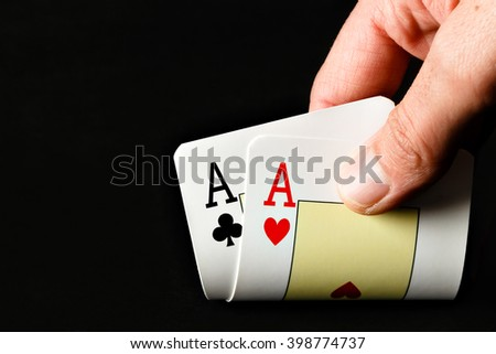 Closeup of poker player with two aces on black background. Horizontal image.