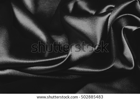 Closeup of rippled black silk fabric, elegant background for design, black and white background
