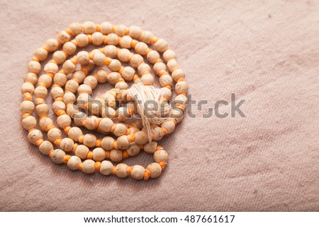Closeup of rolled Indian japa mala chanting beads on woolen texture
