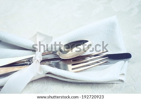 Closeup of Silverware tied in satin ribbon and a cloth napkin on cream white damask tablecloth from above.  Horizontal, vintage instagram