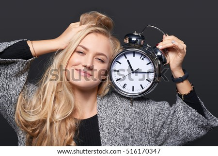Closeup of smiling woman stretching herself holding big alarm clock, over grey background