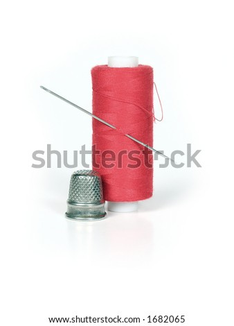 closeup of tailors tools - spool of thread with a needle stuck in it and a thimble
