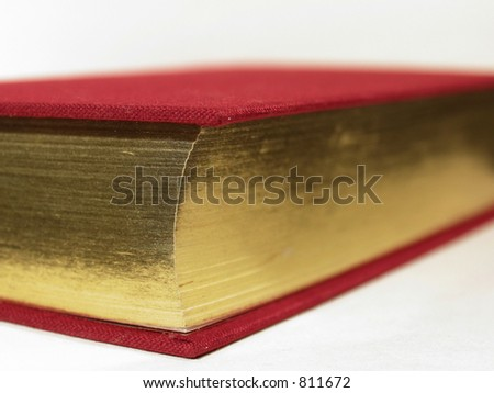 Closeup of the corner of a gold-gilded book with a red cover.