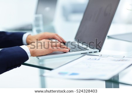 closeup of the hands of the financier on the laptop to work on the laptop keyboard. on the screen of the laptop - the financial schedule. nearby are the financial documents