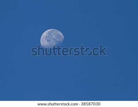 closeup of the moon during the day in a blue sky