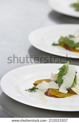Closeup of three plates of salads with grated cheese