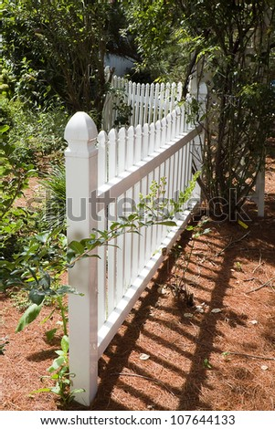 Closeup of white picket fence in garden