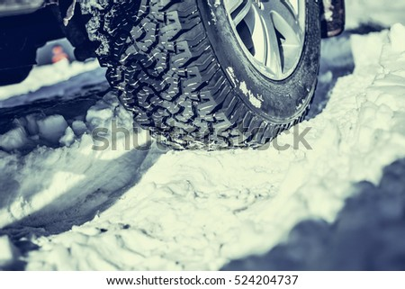 Closeup of winter tyre on a snowy road