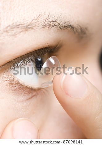closeup of woman inserting a contact lens into the eye