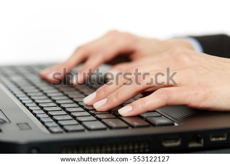 Closeup of woman's hands over laptop keyboard, typing