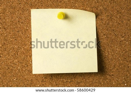 closeup of yellow note paper on cork board with curl corner