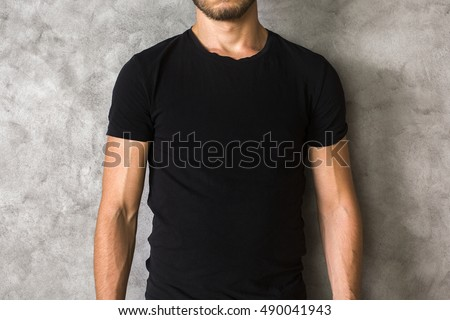 Closeup of young man's body in empty black t-shirt on textured concrete wall background. Mock up