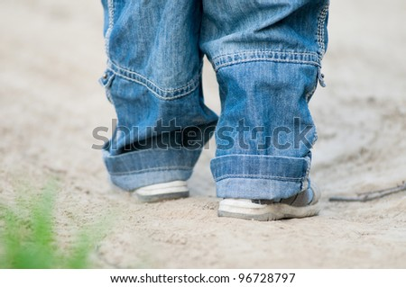Closeup on a kids feet wearing grey sandals and jeans over ground