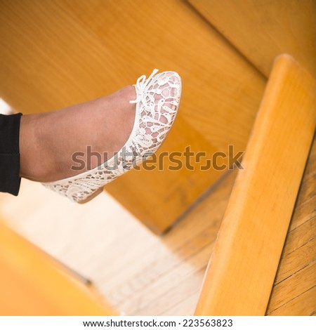 Closeup on human foot with white shoe of young woman sitting at her wood desk