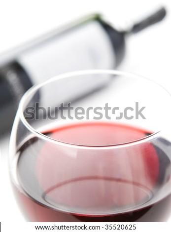Closeup on rim of the glass filled with red whine. Blurred bottle of wine in background.