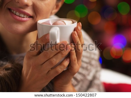Closeup on young woman with cup of hot chocolate with marshmallow in front of christmas lights