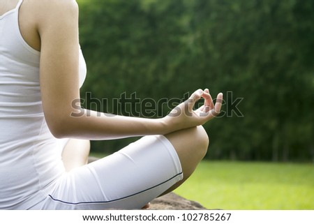 Closeup photo of a asian woman in yoga position. Shot outdoor during summer