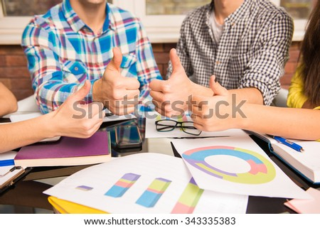Closeup photo of a young group showing thumbs up working on business plan