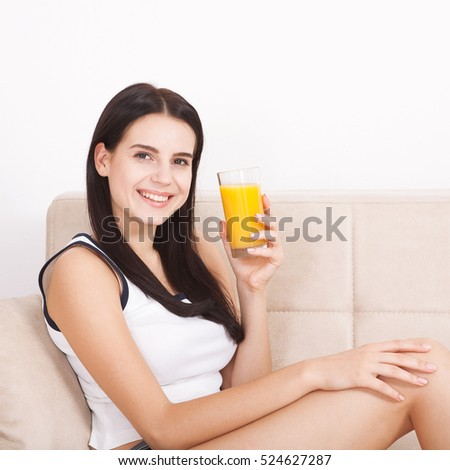 Closeup photo of sexy young woman drinking orange juice. Beautiful face and clear skin woman close up