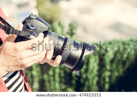 Closeup picture of woman hand holding camera and preview photos indoor