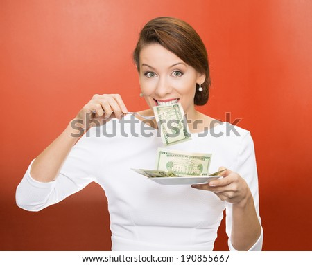 Closeup portrait greedy, young ceo, corporate executive, business woman, manager eating green cash, money dollars from plate, isolated red background. Emotion, facial expression. Financial avarice.
