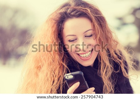 Closeup portrait, happy, cheerful, girl, excited by what she sees on cell phone, isolated park city street background. Facial expression, reaction. Beautiful woman sending text message from her mobile