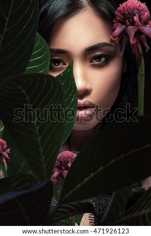 Closeup portrait of a beautiful Asian woman with plant leaves.