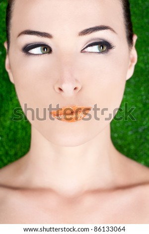 Closeup portrait of a beautiful suspicious woman looking away in studio against green