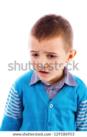 Closeup portrait of a disappointed cute little boy against white background