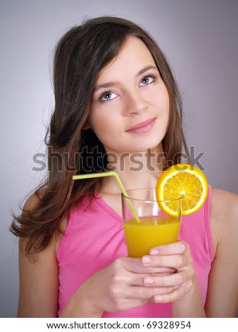 Closeup portrait of a girl with a glass of orange juice
