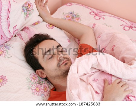 Closeup portrait of a young man sleeping on the bed .