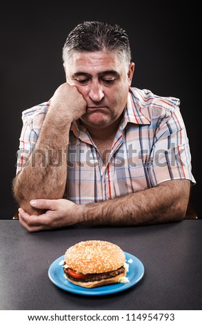 Closeup portrait of an unhappy man looking at burger on gray background