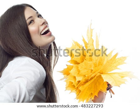 closeup portrait of attractive  caucasian smiling woman brunette isolated on white studio shot lips toothy smile face hair head and shoulders looking up tooth hand holding yellow marple autumn leaves