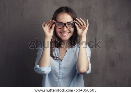 Closeup portrait of beautiful happy young woman with glasses near grey background grunge wall.