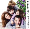 Closeup portrait of cute cheerful family lying down near Christmas tree at home, happy parents with three kids celebrate New Year holiday, love concept - stock photo