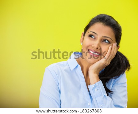Closeup portrait of cute pretty smiling young woman student thinking hand on cheek looking up having idea, isolated on green, yellow background. Positive emotion facial expressions, feelings, attitude