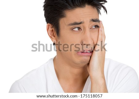 Closeup portrait of depressed young man shaken up crushed by terrible news almost crying, hand on face, isolated on white background. Negative emotion facial expression feelings, reaction, situation