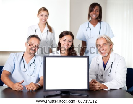 Closeup portrait of doctors and nurses in a meeting with a monitor in the foreground